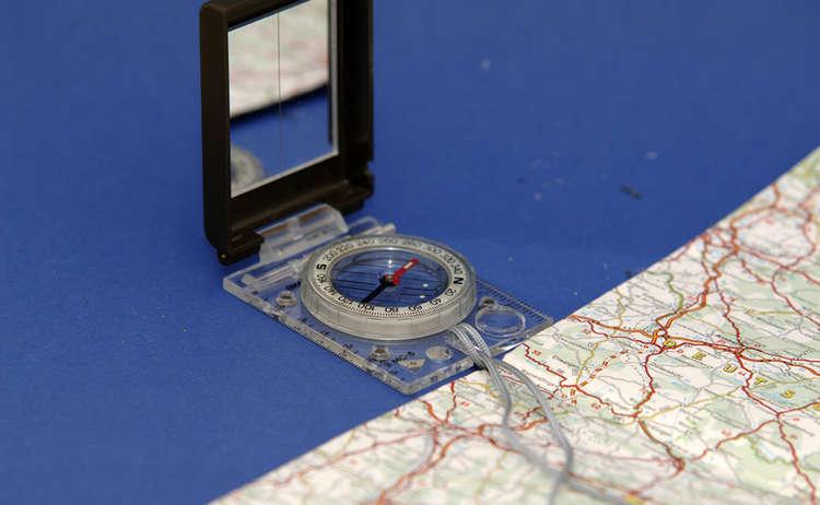 4) Deshalb benötigt der Kompass ein eckiges Gehäuse: Dieses wird an die Außenkante der Karte gelegt und beides so lange gedreht, bis Kompass- und Karten-Norden übereinstimmen.