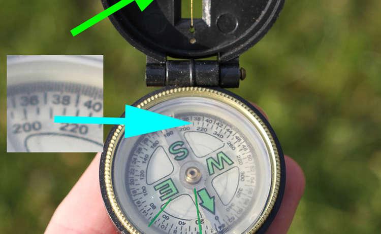 6) Um die Marschzahl herauszufinden, wird über Kimme (rot) und Peilschlitz (grün) das Marschziel anvisiert. Auf der Kompassrose kann dann die Marschzahl (blau) abgelesen werden – in diesem Fall 210 Grad.