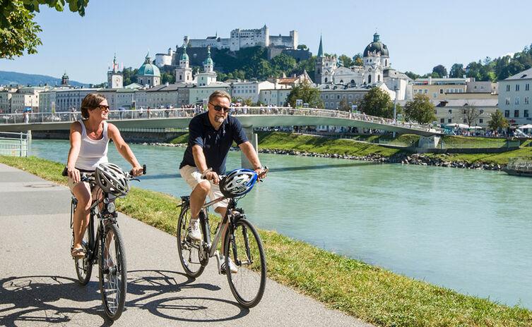 Radfahrer am Ufer der Salzach in der Salzburger Altstadt