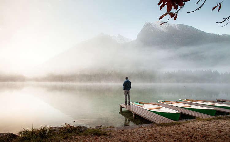 Ein Wanderer genießt den Morgen am Hintersee im Bergsteigerdorf Ramsau